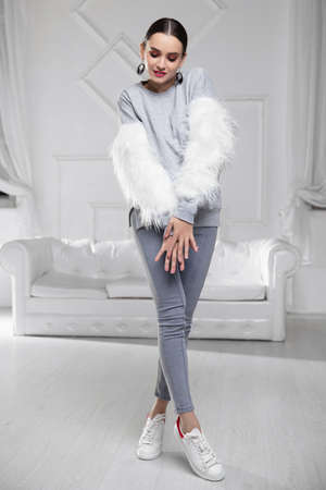 Cute woman wearing a sweater with fur and jeans posing in studio Stock Photo