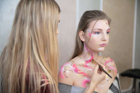 The artist applies makeup to a cute young model in the studio Stock Photo