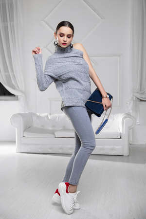 Beautiful woman dressed in a sweater and jeans with a blue clutch in her hands