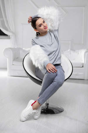 Nice brunette wearing a sweater with fur and jeans sitting on an armchair