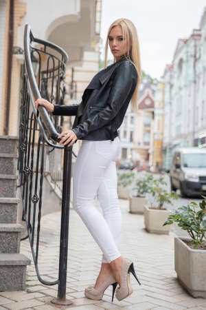 lovely blonde posing near the stairs on the background of buildings, dressed in a jacket, pants and corset Фото со стока