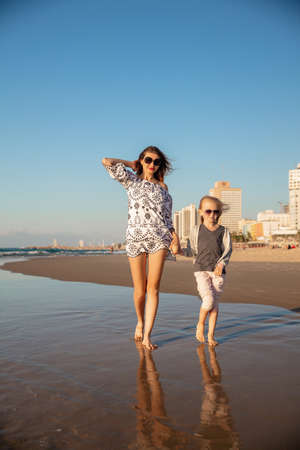 Mom with a daughter walking barefoot along the surf on the sand beach