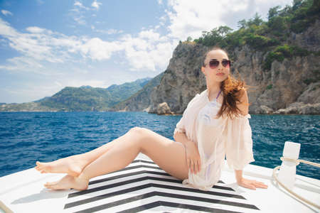 Young pcharming woman posing on a yacht on a background of mountains and the sea, dressed in a swimsuit and tunic