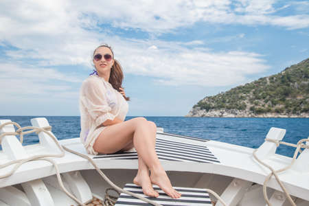 Young cute woman posing on a yacht on a background of mountains and the sea, dressed in a swimsuit and tunic