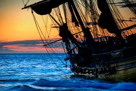 brig ship: Beautiful sunrise beside a little sailboat bergantn Stock Photo