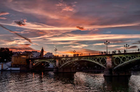 Beautiful Triana bridge next to the Guadalquivir river on its way through the city of Seville, Andalusia Фото со стока