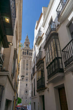 The Giralda view from the narrow streets of the city of Seville