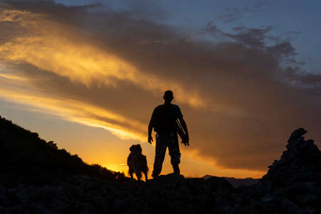 The hiker who walks with his dog at sunset in the mountain