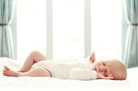 enfant qui dort: Nouveau-né dort sur une couverture blanche en face de la fenêtre. Soft focus, DOF peu profond.