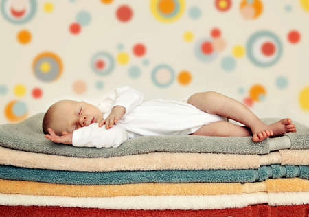 Newborn baby sleeping on colorful towels. Soft focus, very shallow DOF. Stock Photo