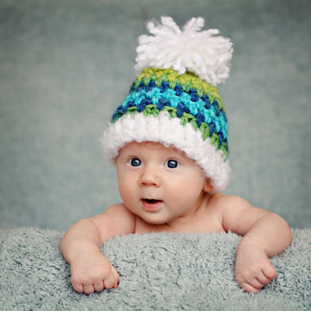 Curious, happy, two months old baby posing on blue blanket. Stock Photo - 13044731