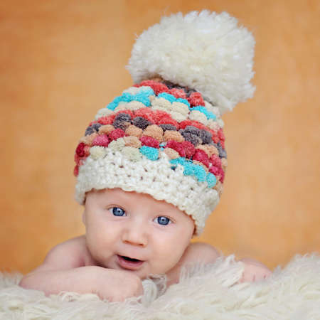 Curious, happy, two months old baby in cute hat