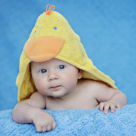 Curious, happy, three months old baby posing on blue blanket with yellow towel Stock Photo