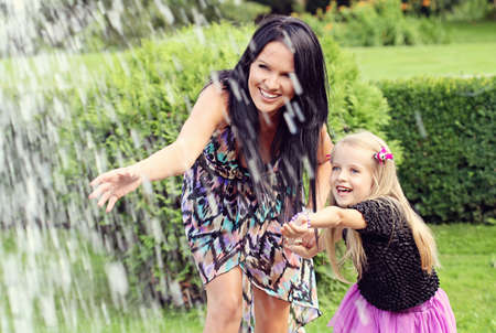 Beautiful young mother with her five years old daughter playing with fountain water in the park Banco de Imagens