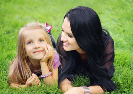Beautiful young mother with her five years old daughter laying on the grass
