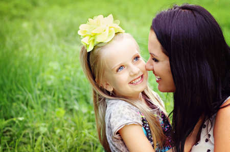 Beautiful young mother with her five years old daughter playing on the grass Stock Photo