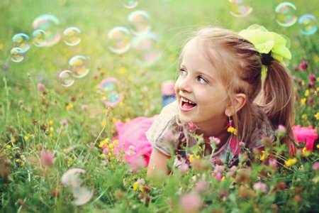 burbujas de jabon: Dulce, feliz, sonriente niña de seis años de edad, por la que se sobre un césped en un parque jugando con burbujas y riendo