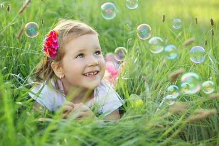 pompas de jabon: Dulce, feliz, sonriente ni�a de tres a�os de edad, por la que se sobre un c�sped en un parque jugando con burbujas