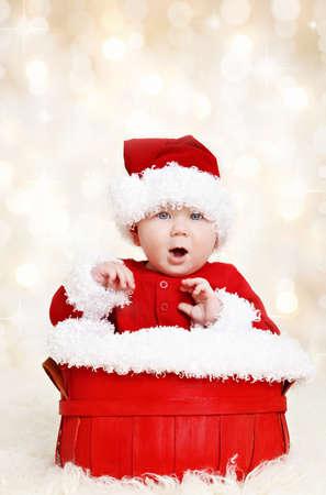 baby kerst: Leuke gelukkige baby in rode kerst kerstman kleren zitten in een mand op defocused lichten achtergrond