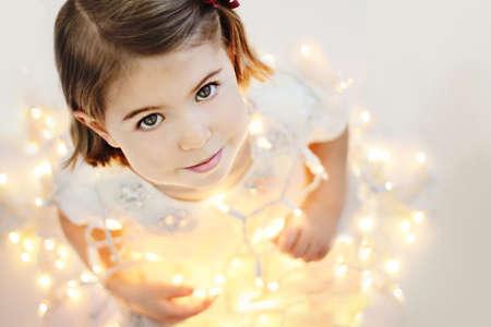 귀여운, 미소, 행복 세살 소녀 빛나는 크리스마스 조명과 함께 앉아