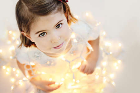Cute, smiling, happy three years old girl sitting with glowing Christmas lights Standard-Bild