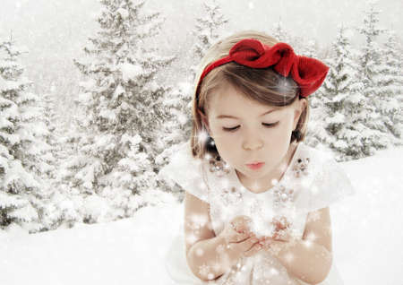 Beautiful little girl blowing snowflakes in white winter forest covered with snow Stock Photo