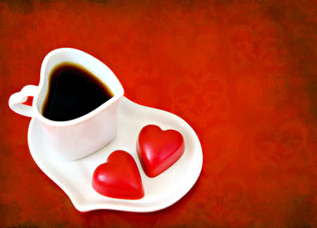 Heart shaped coffee cup with red chocolates on grunge background