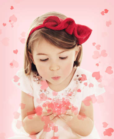Cute three years old girl blowing confetti Valentine hearts on pink background