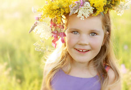 Happy smiling 3 years old girl in colorful wild flowers wreath on a sunny summer meadow field Stock Photo - 21465642