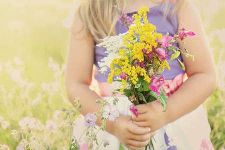 日当たりの良い夏の草が茂った草原フィールドに野生の花の花束を保持している小さな女の子