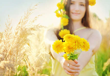 Pretty girl with yellow flowers crown in the grassy sunny summer field holding bouquet Stock Photo
