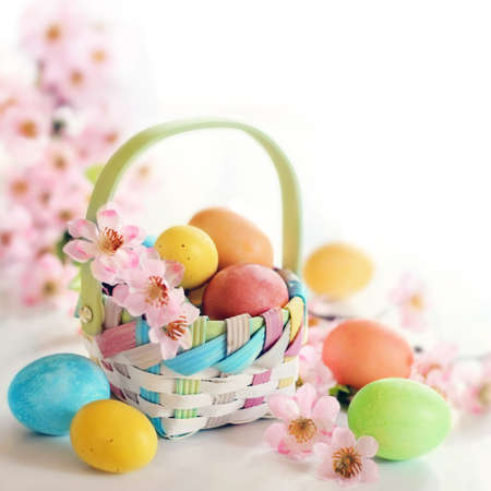 Colorful Easter egs and pink spring flowers in a basket on white background Stock Photo - 27585894