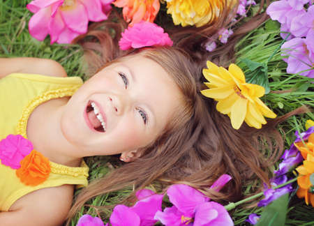 Smiling, happy little summer girl laying on the grass field with flowes Banco de Imagens