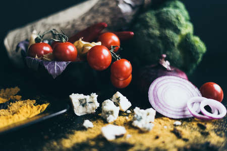 processed grains: A bottle of red wine, delicious fresh tomatoes cherry and red hot chili peppers in a black dish lying on a wooden cutting board. Herbs, blue cheese, a red onion and broccoli are used as a decoration.