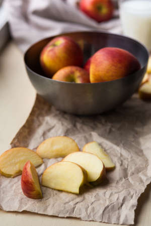 ration: Fresh red apples in a stylish iron dish lying on a white window sill. Apple slices and a glass of milk are used as decoration.