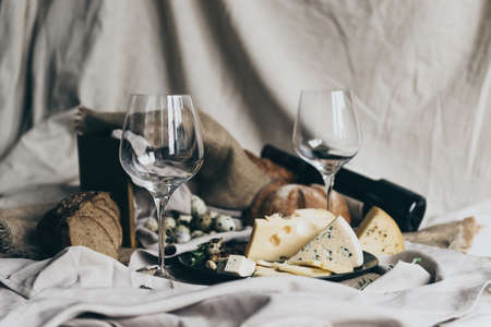 Two empty wineglasses are standing ready to be filled with dry red wine lying behind. Fresh bread, blue cheese, masdaam cheese and quail eggs are used as decoration. stylish shot Stock Photo