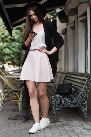 newsfeed: A stylishly dressed girl is standing near the marble coffee table and a wooden bench and flipping newsfeed in facebook. She is wearing a summer white dress, a black jacket and a black hat. Fashion photo