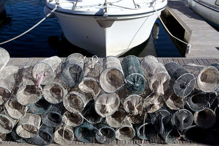 lobster boat: Lobster pots on a quay with boat