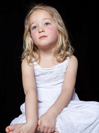 contemplative: Portrait of a contemplative young girl on black background.