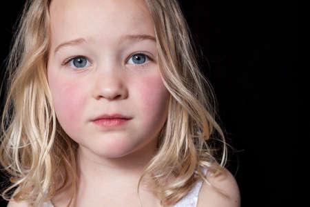 petite fille triste: Close up portrait d'une jeune fille sur fond noir.