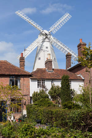 19th: 19th Century Windmill behind some old houses Stock Photo