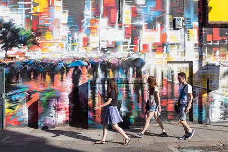 젊은 사람들이 Camden 타운, 런던에서 형형색색 칠한 벽을지나 걸어. 에디토리얼