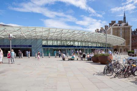 사람들은 런던의 킹스 크로스 역 (King 's Cross Station)에서 출발 홀 밖에서 기다립니다.