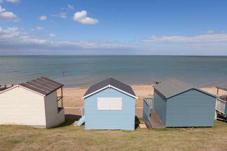 Row of pastel painted wooden beach huts. Stock Photo