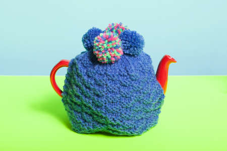 cosy: Teapot with knitted cosy Stock Photo