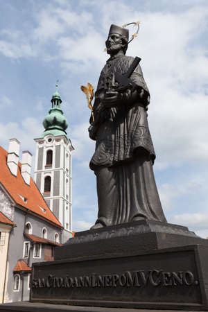 Statue with St. Jost Church by the river in historic Cesky Krumlov, Czech Republic.