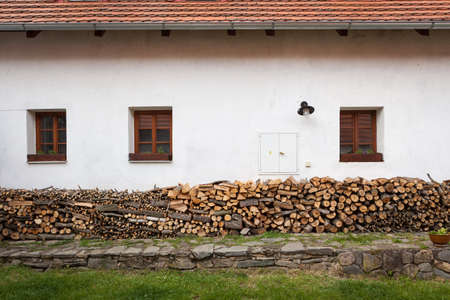 Chopped firewood piles against the side of a rural building Stock Photo