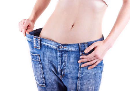 woman shows her weight loss by wearing an old jeans, isolated on white background Stock Photo - 18127369