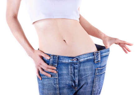 large woman: Slim woman shows her weight loss by wearing an old jeans, isolated on white background
