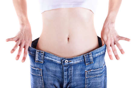 loose weight: Slim woman shows her weight loss by wearing an jeans, isolated on white background